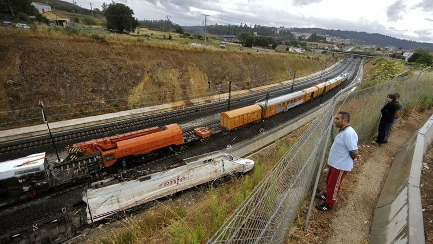 """People look at part of a train that crashed in Angrois, near Santiago de Compostela, on July 27, 2013. The Spanish train was hurtling around a curve at 179 kph (111 mph), more than twice the speed limit, when it leapt off the tracks in a disaster that killed 79 people, a report on the contents of the """"black box"""" recorders showed."""
