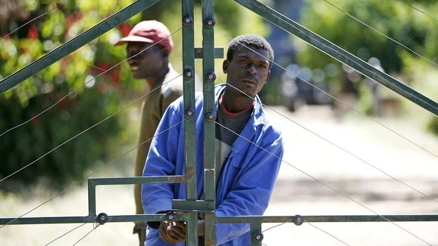 In this file photo, two men are seen by the the gates of a farm which they seized from white farmers, in Chegutu, 120 km south-west of Harare, on April 17, 2009. Robert Mugabe's apparent landslide election victory has prompted fears that Zimbabwe's barely resuscitated economy is in for another bumpy ride.