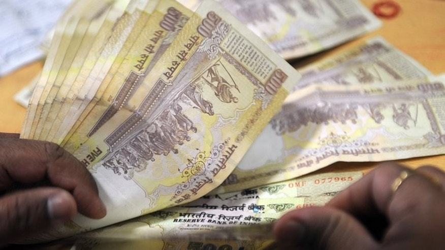 A bank cashier counts Indian rupee notes at a bank in Mumbai on November 22, 2011. India's central bank was believed to have intervened in the foreign exchange market Friday to rescue the rupee from near-record low levels, dealers said.