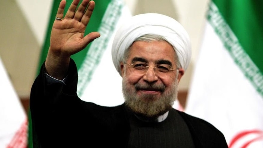 A picture taken on June 17, 2013 shows Iranian president-elect Hassan Rowhani waving as he attends a press conference in Tehran. Rowhani says Israel is a foreign body that must be removed, and also cast doubt on efforts to revive peace talks with the Palestinians.