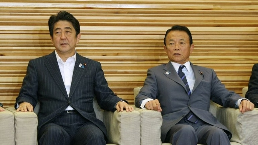 Japanese Prime Minister Shinzo Abe (L) and Deputy PM Taro Aso attend a cabinet meeting in Tokyo, on August 2, 2013. Gaffe-prone Aso rejected calls for his resignation after stoking international condemnation by saying Tokyo could learn from the Nazis' swift overhaul of Germany's constitution.