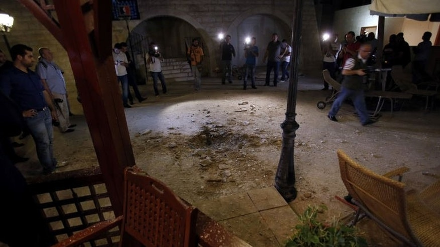 Journalists inspect the damage at a private residence where one of two rockets fired from an unknown location exploded in the early hours of August 2, 2013, just metres from an entrance to the presidential palace in Baabda.