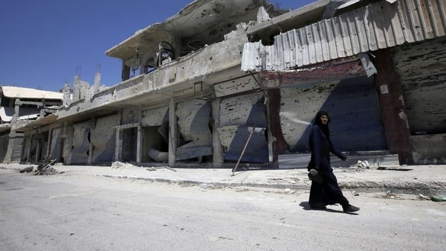 A Syrian resident walks through a devastated street in Qusayr, on August 1, 2013. Qusayr has been the scene of some of the fiercest combat in the Syrian conflict and has been almost completely deserted by its 50,000 former inhabitants