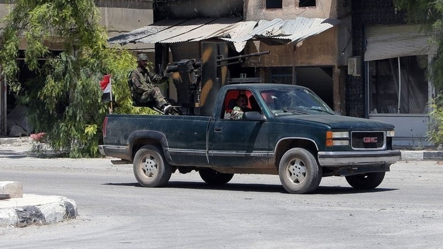 Syrian soldiers patrol a street of the city of Qusayr, on August 1, 2013. Qusayr has been the scene of some of the fiercest combat in the Syrian conflict and has been almost completely deserted by its 50,000 former inhabitants