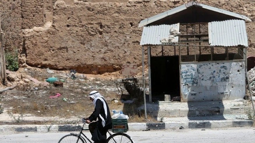 A Syrian resident rides his bicycle through Qusayr, on August 1, 2013. Qusayr has been the scene of some of the fiercest combat in the Syrian conflict and has been almost completely deserted by its 50,000 former inhabitants