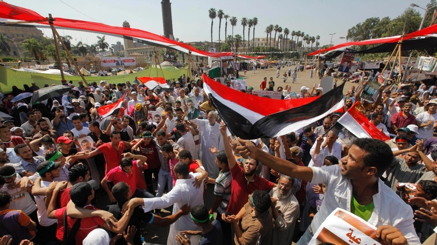 "Aug.2, 2013 - Supporters of Egypt's ousted President Mohammed Morsi shout slogans at a rally near Cairo University in Giza, Egypt. Arabic reads, ""to legitimacy."""