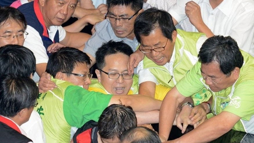 "Taiwan legislators scuffle with each other in reaction to a bill due to pass on whether to rebuild the fourth nuclear power plant, at parliament in Taipei, on August 2, 2103. Dozens of lawmakers from opposing camps clashed as they tried to seize the chamber's podium and splashed water from cups and plastic bottles at each other as some shouted ""Support for Nuke 4 harms children."""