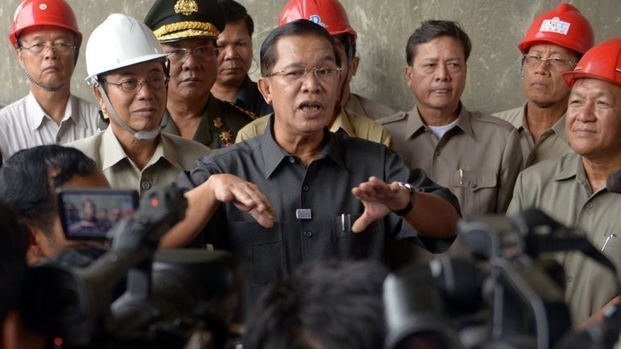 Cambodian Prime Minister Hun Sen (C) speaks to the media during his visit to a construction site in Phnom Penh on July 31, 2013. Hun Sen last Sunday claimed it had secured an estimated 68 of the 123 lower house seats, defeating the CNRP which won 55.
