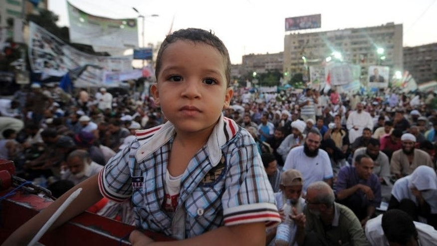 "An Egyptian boy poses for the camera as supporters of the deposed president Mohamed Morsi attend the sit-in at Rabaa al-Adawiya square in Cairo on August 3, 2013. Tensions have mounted over a looming police move to dismantle two Cairo sit-ins by Morsi loyalists, though Fahmy insisted that authorities had ""no desire to use force if there is any other avenue that has not been exhausted."""