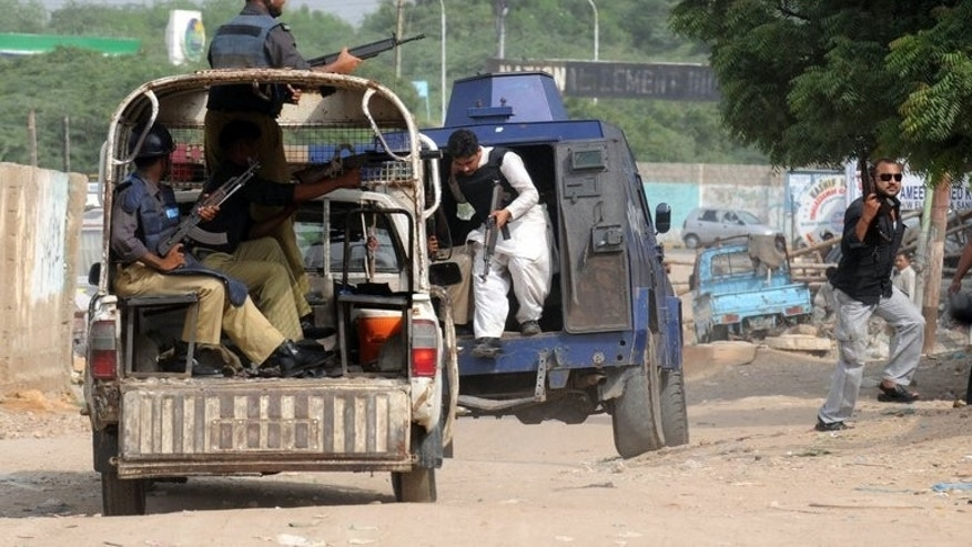 Pakistani police in vans patrol a troubled eastern neighbourhood of Karachi on August 4, 2010. Gunmen shot dead four policemen on a patrol in the southern Pakistani port city of Karachi Saturday, police said.