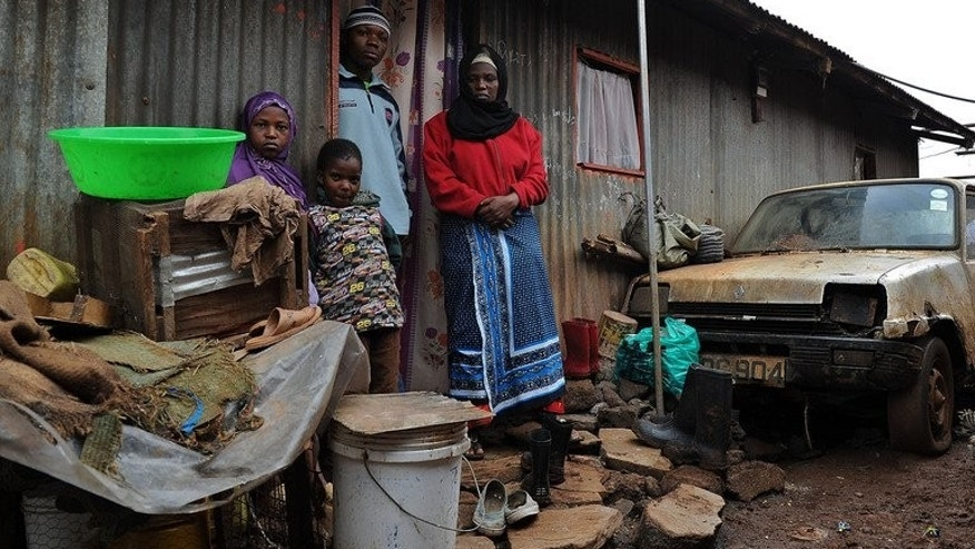 Latifah Naiman (R), 38, stands with her three children in front of her single-roomed house in the Nairobi slum of Kangemi on August 3, 2013. Naiman says she cannot support her family after her husband was killed in a road crash involving an American diplomat who has since left the country.