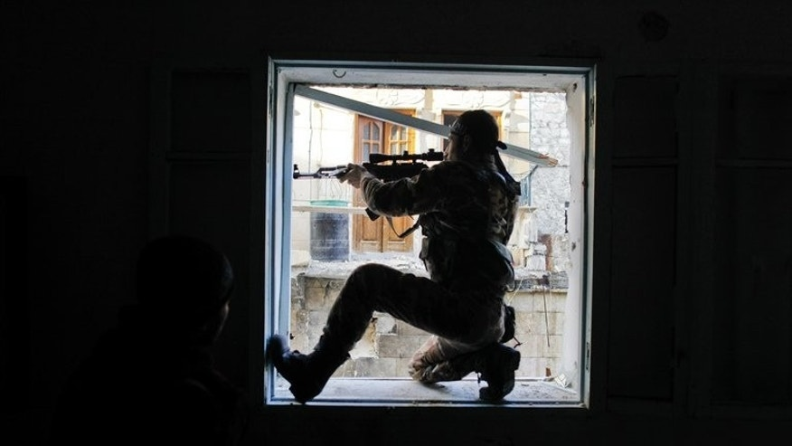A Syrian rebel aims at a regime forces during clashes in the Karmel al-Jabl district of Aleppo, on December 6, 2012. Two Islamist Lebanese-Swedish brothers who left their Scandinavian home for Lebanon, have died fighting alongside Syrian rebels in Homs province, their cousin and a local cleric tell AFP.