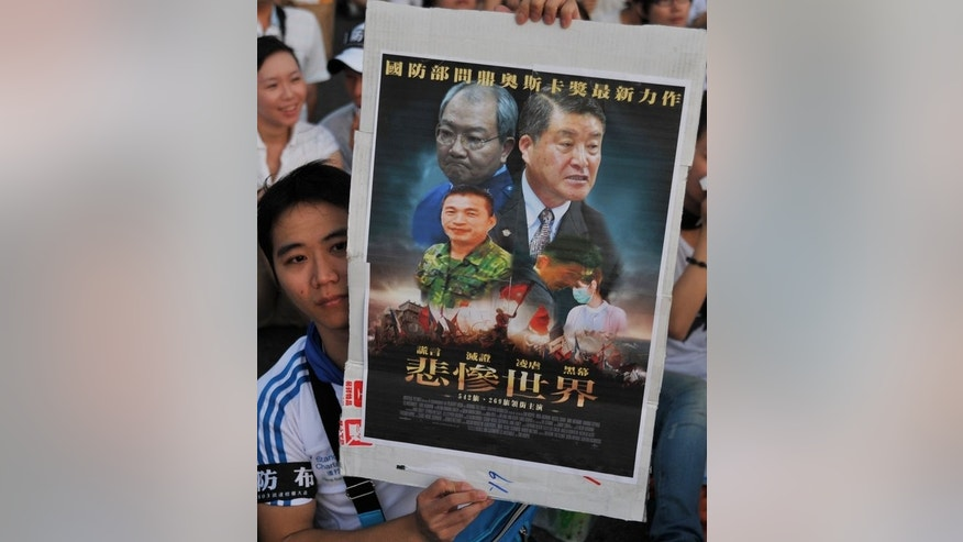 A Taiwanese protester holds a placard -- detailing a case involving a young conscript who died after alleged abuse while serving with the military -- during a rally in Taipei, on August 3, 2013. More than 100,000 Taiwanese people have demonstrated in protest over the death of a young conscript who was allegedly abused in the military.