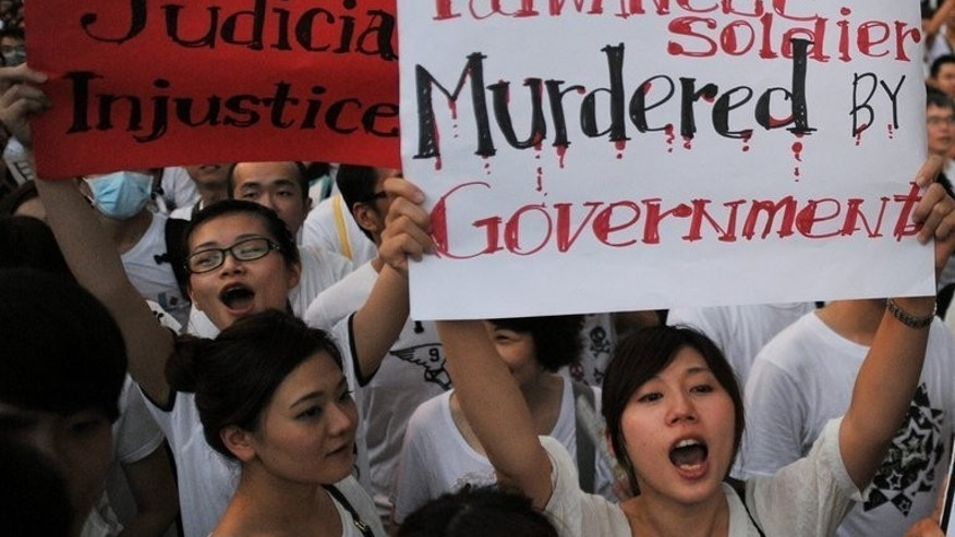 Taiwanese protesters shout slogans and hold placards during an anti-military rally in Taipei, on August 3, 2013. More than 100,000 Taiwanese people have demonstrated in protest over the death of a young conscript who was allegedly abused in the military.