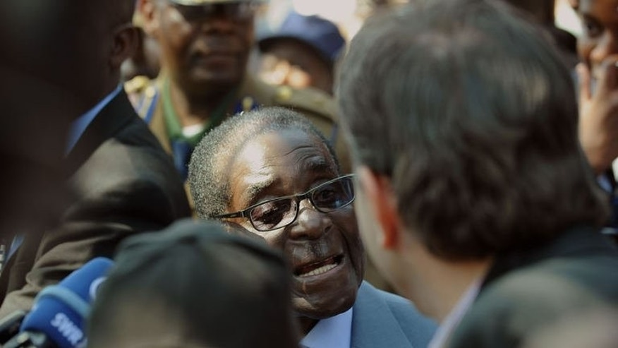 Zimbabwe President Robert Mugabe (C) answers journalists questions after voting at a polling station at a school in Harare on July 31, 2013. Mugabe was declared the run-away winner of Zimbabwe's controversial presidential election Saturday, extending his 33-year rule.