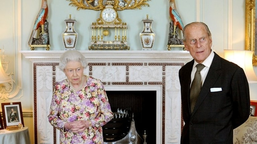 Britain's Queen Elizabeth II waits with Prince Philip, Duke of Edinburgh (R) at Buckingham Palace in central London on June 6, 2013. Prince Philip, 92, is to appear in public this month for the first time since having surgery on his abdomen in June, Buckingham Palace has announced.