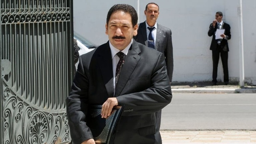Tunisian Interior Minister Lotfi Ben Jeddou (C) arrives for a meeting with various political parties at the Prime Minister's office in Cathage on August 3, 2013.