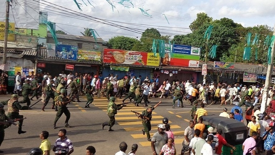 Sri Lankan troops chase local residents protesting against the alleged poisoning of drinking water in the village of Weliweriya, on August 1, 2013. A second protester has died from wounds suffered when troops fired on villagers demonstrating against contaminated water supplies, as tensions remain high in the area.