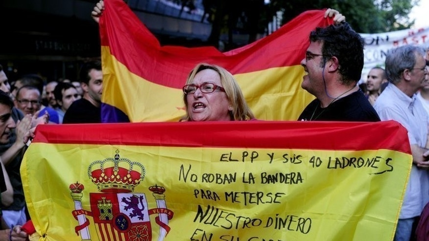 "A woman holds a Spanish flag reading ""PP and his 40 thieves, they are stealing our flag to put money in their wallet"" as she protests outside the Popular Party (PP) headquarters in Madrid, on July 18, 2013. Spaniards overwhelmingly believe Prime Minister Mariano Rajoy lied when he denied being corrupt after his name appeared in a slush fund scandal, according to an opinion poll in El Mundo."