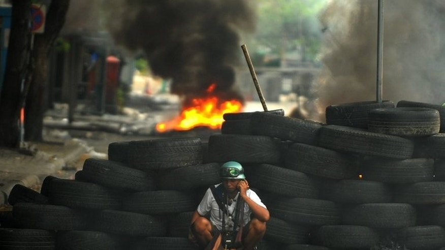 A Thai ''Red Shirt'' protester sits behind a tyre barricade during clashes in Bangkok, on May 16, 2010. Thailand's Prime Minister Yingluck Shinawatra has expressed fears that violence could erupt during planned anti-government protests in Bangkok this weekend, following unrest at multiple rallies in the capital over recent years.