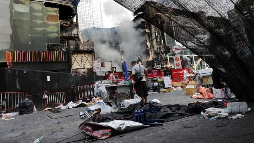 Thai civilians walk through a dismantled anti-government protest camp in Bangkok, on May 20, 2010.