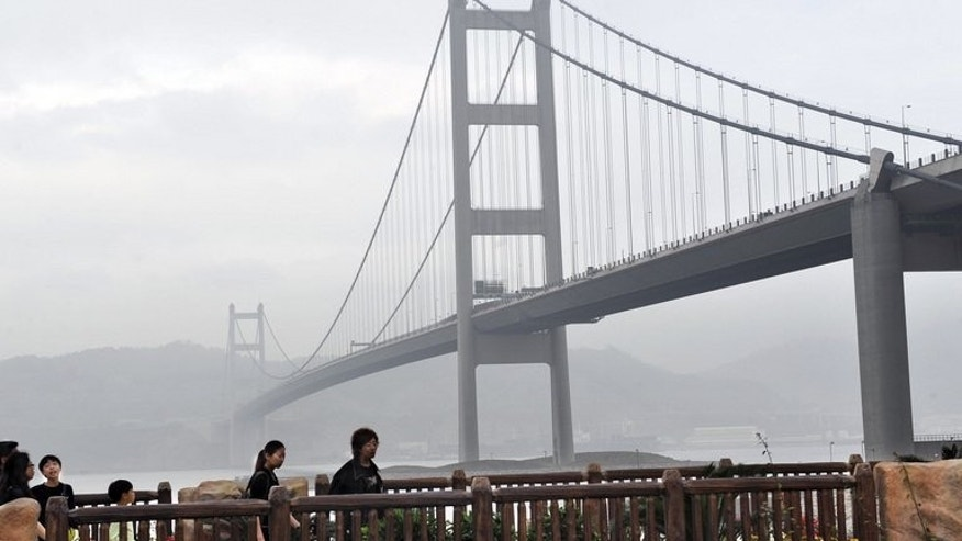 Visitors walk along a pathway near the Tsing Yi bridge in Hong Kong on February 15, 2009. Two people died and a third is missing after a boat sank in Hong Kong waters near the bridge Saturday, amid ongoing public concerns over the city's maritime safety following a fatal ferry crash last October.