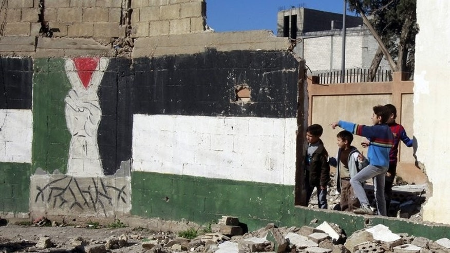 """Children from the refugee """"Camp of Palestine"""" in Syria's central city of Homs watch a UN convoy, on January 21, 2013."""