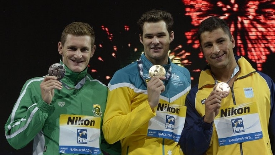 Gold medalist Australia's Christian Sprenger (C), silver medalist South Africa's Cameron Van Der Burgh (L) and bronze medalist Brazil's Felipe Lima celebrate on the podium during the award ceremony of the men's 100m breaststroke event in the FINA World Championships at Palau Sant Jordi in Barcelona, on July 29, 2013.