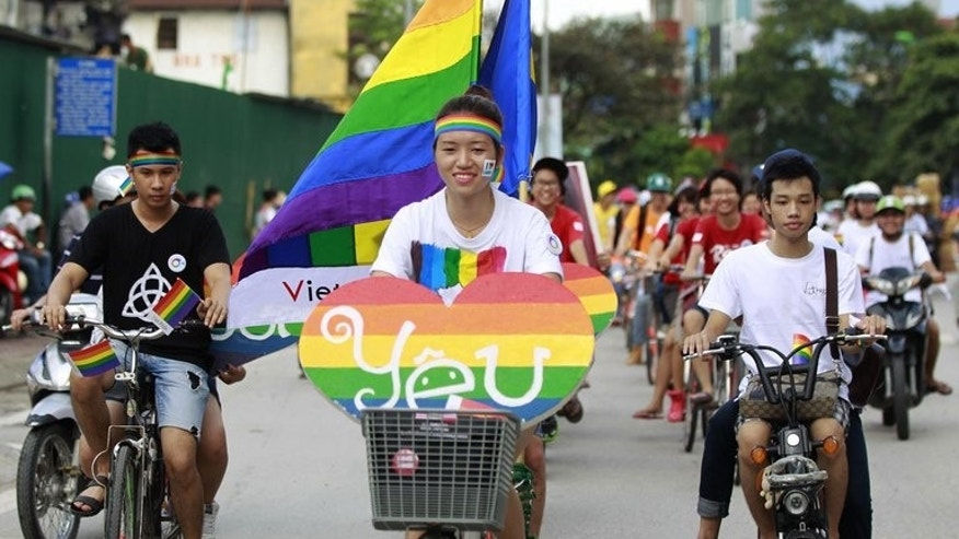 Activists ride on their bikes during a local annual gay pride parade in Hanoi, on August 4, 2013. Some two hundred activists waving rainbow flags and carrying hand-painted banners biked in a colourful convoy as part of the communist country's second gay pride parade.