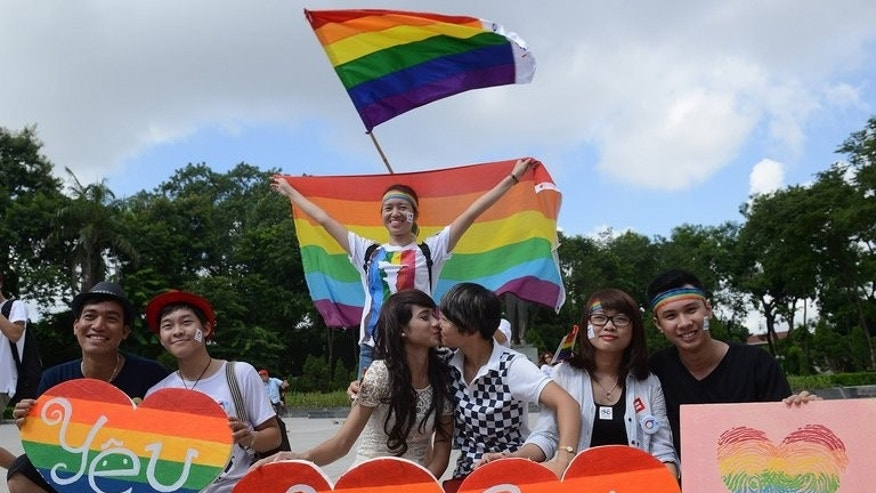 Participants pose for a photo during a local annual gay pride parade in Hanoi, on August 4, 2013. Some two hundred activists waving rainbow flags and carrying hand-painted banners biked in a colourful convoy through central Hanoi as part of the communist country's second gay pride parade.