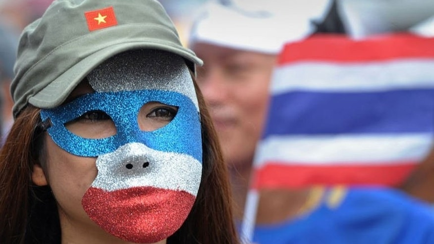 An anti-government protester wearing a mask takes part in a demonstration in Bangkok, on August 4, 2013. Hundreds of Thai protesters have gathered in Bangkok to rally against the government and divisive former premier Thaksin Shinawatra amid worries over the potential for fresh unrest in the politically-turbulent country.