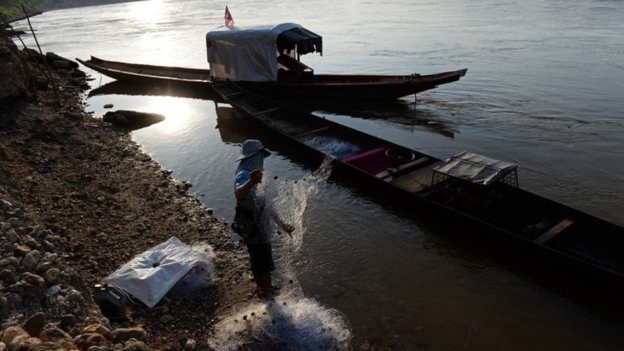 A fisherman stands on the bank of the Mekong river as he checks his net, in Wiang Kaen, a district in the northern Thai province of Chiang Rai bordering Laos, on May 29, 2013. The waters of the mighty Mekong have sustained generations of families but nowadays its fishermen often find their nets empty and fear hydropower mega-dams will destroy their livelihoods.