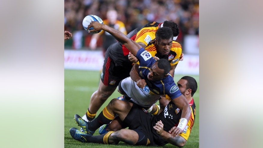 Brumbies' Tevita Kuridrani passes the ball in a tackle from three Chiefs' defenders during the Super 15 final at Waikato Stadium in Hamilton, New Zealand, on August 3, 2013. The Chiefs won 27-22.