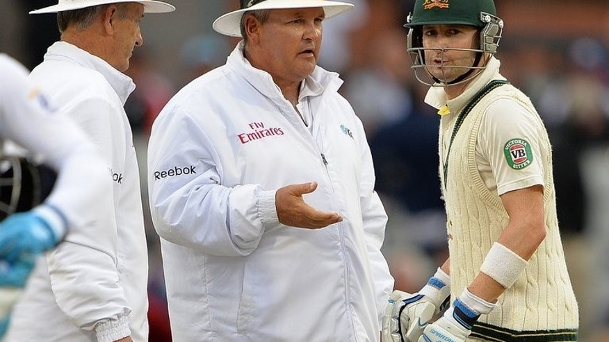 Australia's Michael Clarke (R) reacts as the umpires Tony Hill (L) and Marias Erasmus stop the game due to bad light during the third Ashes Test match in Manchester on August 4, 2013. Clarke was furious after the umpires took the players off the field for bad light in the third Test against England at Old Trafford.
