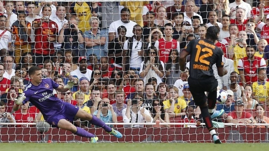 Galatasaray's Ivorian striker Didier Drogba scores a penalty past Arsenal's Polish goalkeeper Wojciech Szczesny (L) during the pre-season friendly football match between Arsenal and Galatasaray at The Emirates Stadium in north London on August 4, 2013. Galatasaray won 2-1.