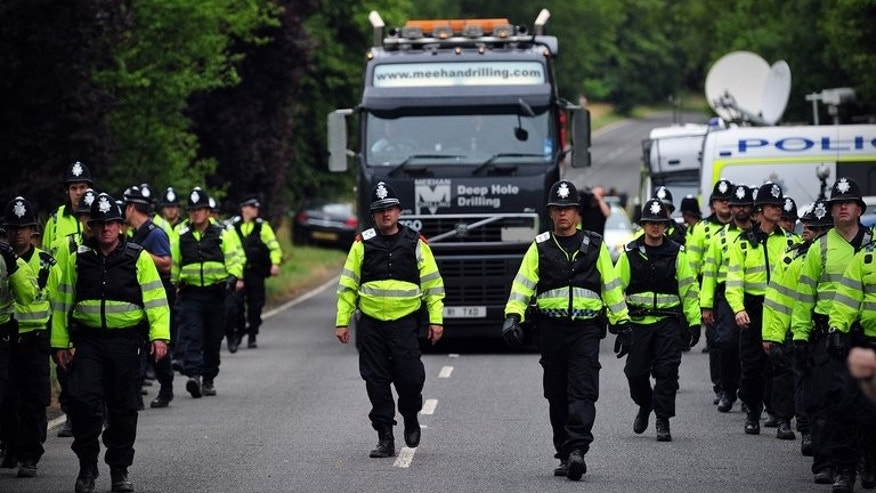 Police personnel escort a lorry to the entrance of a drill site operated by Cuadrilla Resources in Balcombe, England, on July 31, 2013.