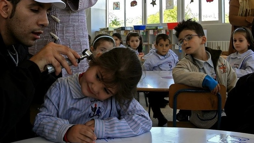 A volunteer checks a student before giving her a polio vaccine in the city of Nabatiyeh, Lebanon on October 31, 2006. Israel on Monday launches a mass campaign in the south of their country to vaccinate 200,000 children up to nine years old against polio, Health Minister Yael German said.