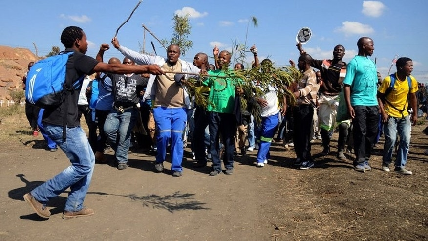 Striking Lonmin mine workers dance and sing while starting to gather next to a hill called Wonderkop in Marikana on May 14, 2013. A militant South African labour union has wrested majority control at the world's richest platinum mines, shaking up the industry and potentially boding ill for the ruling ANC, analysts say.