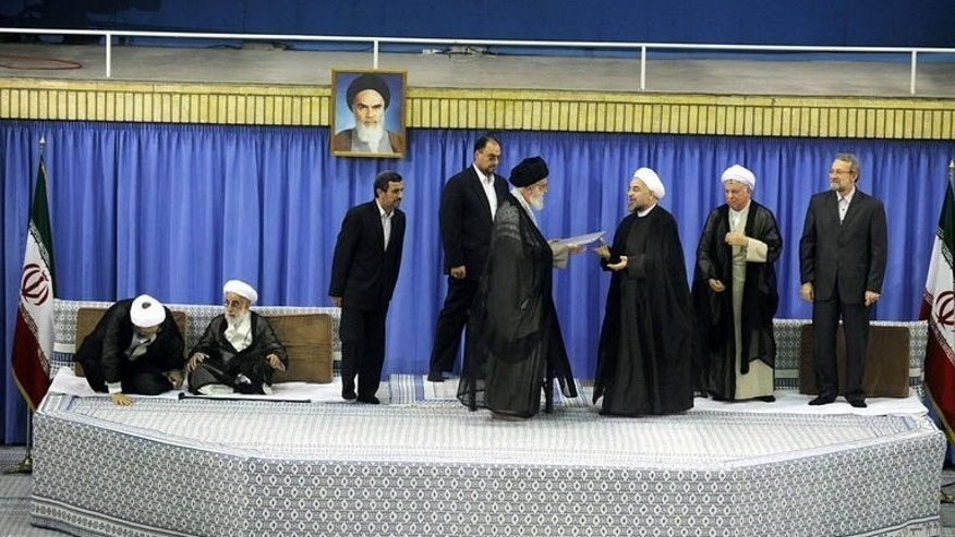 Ayatollah Ali Khamenei (C) officially endorses moderate cleric Hassan Rowhani (3rd right) during a ceremony in Tehran, on August 3, 2013. Rowhani has vowed to work to lift the international sanctions imposed on Tehran over its controversial nuclear drive.
