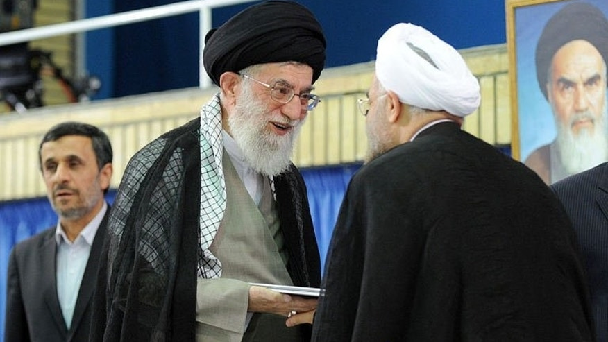 Iranian supreme leader Ayatollah Ali Khamenei (C) officially endorses moderate cleric Hassan Rowhani during a ceremony in the capital Tehran on August 3, 2013, as former president Mahmoud Ahmadinejad (L) stands by.