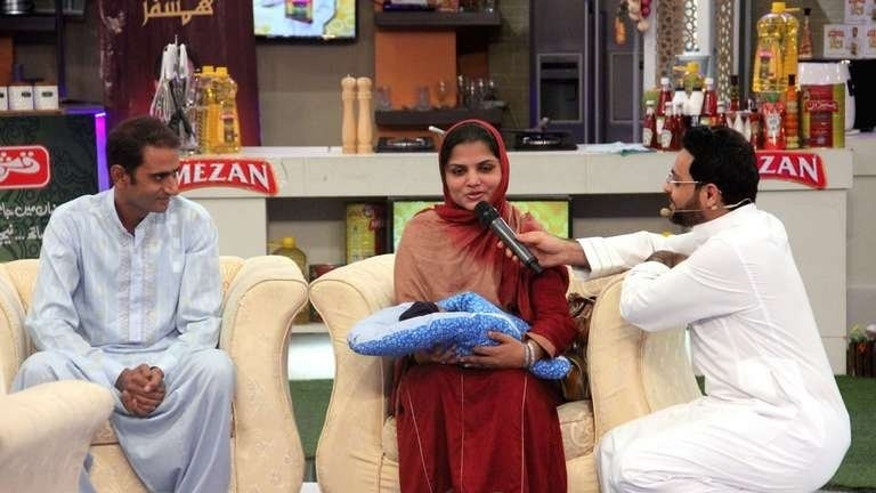 In this photo, taken on August 2, 2013 and released by Geo television shows Pakistani television show host Aamir Liaqat Hussain (R) as he speaks with Farha Jabeer (C) after she adopted a baby boy Aman Ali as her husband Jabeer Ali looks on during an Islamic quiz show for Ramadan in Karachi.
