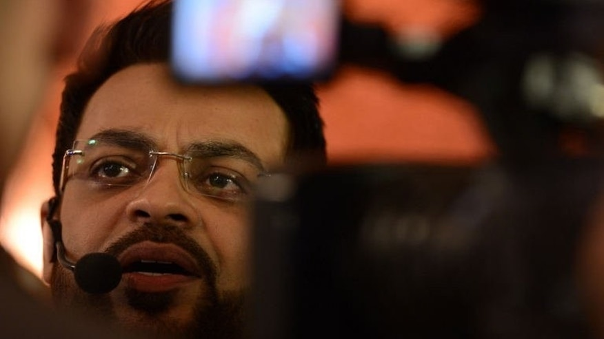 Pakistani television show host Aamir Liaqat Hussain presents an Islamic quiz show for Ramadan in Karachi, on July 31, 2013. The charismatic Muslim preacher criticised for giving out babies to childless couples live on prime-time Pakistani TV denies he is fighting a ratings war and insists he is spreading charity.