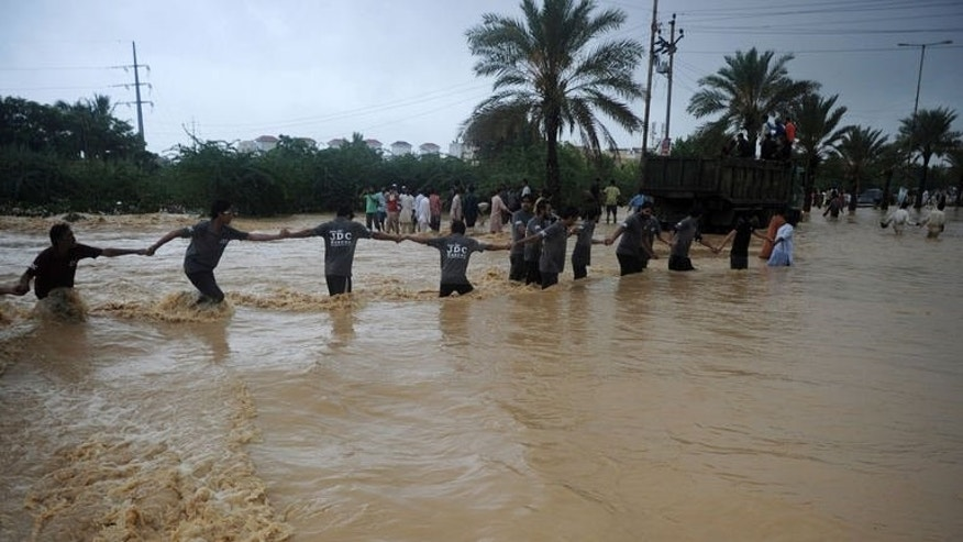 Pakistani rescuers form a chain as they prepare to evacuate residents from a flooded area in Karachi, on August 4, 2013. Pakistani disaster relief officials have issued fresh flood warnings after the death toll from heavy monsoon rains rose to 45 and waters paralysed parts of the largest city Karachi.