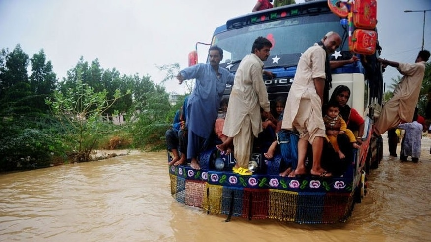 Pakistani residents ride on a truck as they evacuate a flooded area in Karachi, on August 4, 2013. Pakistani disaster relief officials have issued fresh flood warnings after the death toll from heavy monsoon rains rose to 45 and waters paralysed parts of the largest city Karachi.