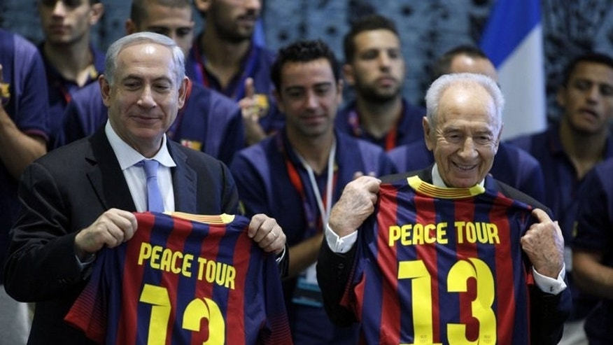 Israeli President Shimon Peres (R) and Israeli Prime Minister Benjamin Netanyahu (L) pose for a picture with Barcelona FC jerseys during a ceremony at the presidential residency in Jerusalem on August 4, 2013.