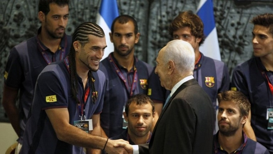Israeli President Shimon Peres (R) welcomes Barcelona FC goalkeeper Jos?? Manuel Pinto during a ceremony at the presidential residency in Jerusalem on August 4, 2013.