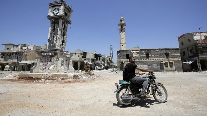 "A Syrian rides his motorbike past the Sunni Grand mosque on August 1, 2013 in the city of Qusayr. Syria's crisis will only be solved by stamping out ""terror"", President Bashar al-Assad said on Sunday, in reference to rebels fighting his regime."