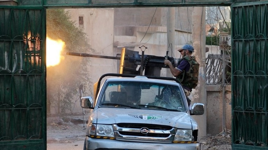 A Syrian rebel fighter fires from a truck during clashes with forces loyal to the regime in Deir Ezzor on August 1, 2013.
