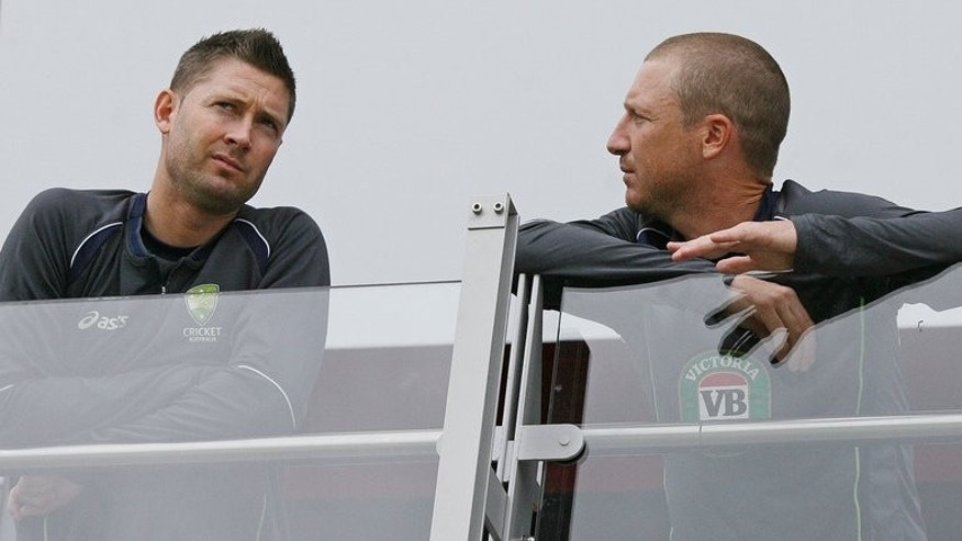 Australian captain Michael Clarke (L) and vice captain Bradley Haddin speak as rain delays the start of play during the fifth day of their third Ashes Test match against England, at Old Trafford in Manchester, north-west England, on August 5, 2013.