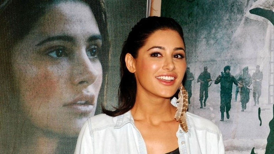 "Bollywood actress Nargis Fakhri ahead of a screening of the film ""Madras Cafe"", in Mumbai, on July 11, 2013. Director Shoojit Sircar describes ""Madras Cafe"", shot in the southwestern Indian state of Kerala, as a ""hardcore political film which examines conspiracies, espionage, how information is coded, decoded and passed through""."